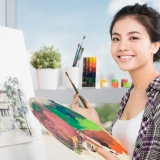 Student Artist smiling with paintbrush and paint palette